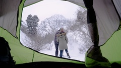 Cute Couple Play In Snow (View From Their Tent) They Jump And Kick The Snow Stock Footage
