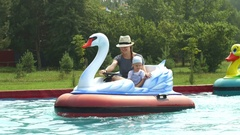 Mother and her little baby boy are rides on swan attraction in a park water pool Stock Footage