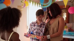 Boy Receiving Present From Girl During Birthday Party At Home Stock Footage