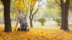 4k footage of young mother running with baby pram at autumn park Stock Footage