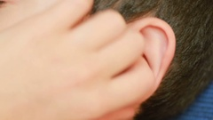 Human child ear close up. earache, otitis. Child touches a sore ear Stock Footage