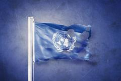 Torn flag of the United Nations waving against grunge background Piirros