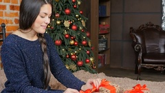 Beautiful girl is opening a Christmas gift. Christmas mood. Slow motion. Stock Footage