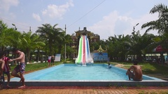 People slide down water chutes at the Dainam amusement park Stock Footage