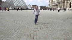 Woman jumps in Louvre palace courtyard Stock Footage