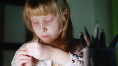 Girl five years draws evening. Beside her vase with colored pencils Stock Footage