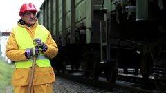 Railway worker looks at the passing train Stock Footage