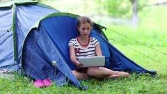 Girl sits on green grass near tourist tent and looks in tablet computer Stock Footage