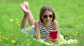 Beautiful girl in sunglasses with red smartphone lies on green grass HD Footage