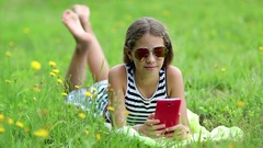 Beautiful girl in sunglasses with red smartphone lies on green grass Stock Footage