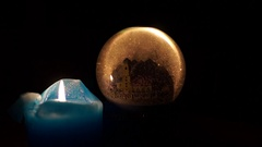A Transparent Round Souvenir Witha Castle in It. One Blue Candle on the Left. Stock Footage