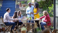 4K Couple celebrating engagement enjoying food & drinks with friends outdoors Stock Footage