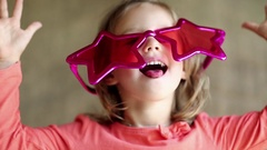 Funny girl in big glasses in the shape of stars looks at the camera and grimaces Stock Footage