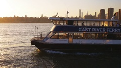 Panning shot of East River Ferry at sunset navigating toward lower Manhattan in Stock Footage