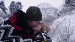 Happy Young Couple Cuddle In Blanket, In Snowy Mountains, They Kiss And Smile Stock Footage