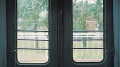 Train closes automatic doors and starts moving along white fence, green trees 4k Stock Footage