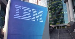 Street signage board with IBM logo. Modern office center skyscraper and stairs Stock Footage
