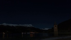 Nigth - winter Curon bell tower appearing from Resia Lake, South Tyrol, Italy Stock Footage