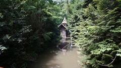Small chalet in the woods next to a stream Stock Footage