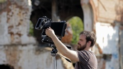 Man adjusts the retro camera among the ruins Stock Footage