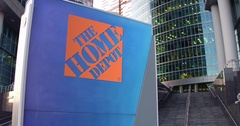 Street signage board with The Home Depot logo. Modern office center skyscraper Stock Footage