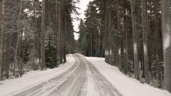 Front view from the car on snowy ice road through the forest Stock Footage