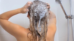 Slow motion video of sexy woman lathering hair at shower	 Stock Footage