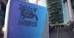 Street signage board with Nestle logo. Modern office center skyscraper and Stock Footage
