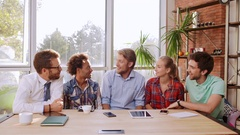 Five interracial males and female sitting at big table with laptop mobile phone Stock Footage