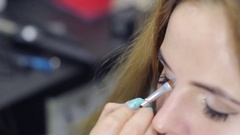 Makeup artist paints eyelashes, makes the shading of the face and eyebrows Stock Footage