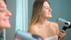 Slow motion footage of brunette woman with long hair using hair dryer at mirror Stock Footage