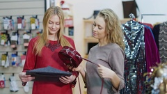 Two stylish lady in a shop of accessories and clothes are choosing handbags Stock Footage