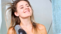 Slow motion portrait of beautiful woman drying hair with blow dryer Stock Footage