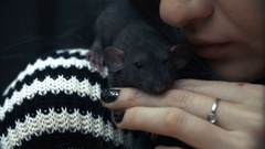 Beautiful lovely girl holds a hand a small home little pet brown mouse close up Stock Footage