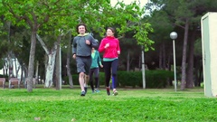 Woman running in the park and having muscle cramp, steadycam shot, slow motion  Stock Footage