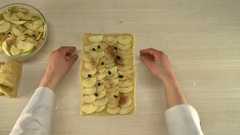 Putting sliced apples on kneaded dough Stock Footage