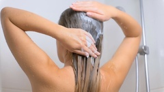 Slow motion footage of young brunette woman washing hair with shampoo Stock Footage
