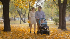 4K footage of happy young family walking with baby pram at autumn park Stock Footage