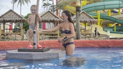 Mother and daughter are having fun in pool bar of hotel Stock Footage