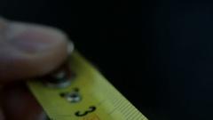 Yellow tape measure, slow motion, black fon. Stock Footage