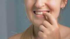 Closeup footage of young woman winkles out piece of food stuck in teeth Stock Footage