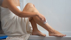 Young woman covered in bath towel removing hair with electric epilator Stock Footage