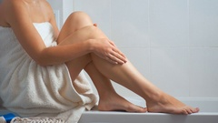 Sexy young woman applying moisturizing creme on legs after bathing Stock Footage