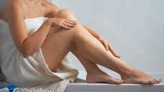 4K closeup footage of sexy young woman sitting at bathroom and applying lotion Stock Footage