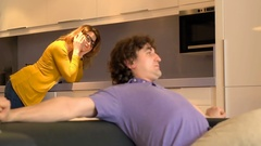 Man stretches his muscles while his girlfriend talks on cellphone in the kitchen Stock Footage