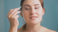 Closeup 4K footage of young woman plucking eyebrows at bathroom Stock Footage