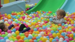 Two children are playing with colored balls Stock Footage