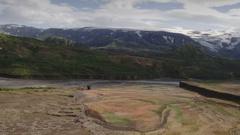 Wide shot of river flowing near mountain range / Thorsmork, Rangarvallasysla Stock Footage
