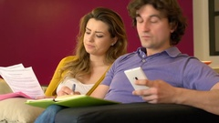 Couple sitting on the sofa and checking documents and outcomes Stock Footage
