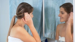 Beautiful young woman looking at her reflection in mirror at bathroom Stock Footage